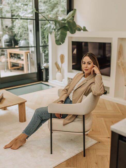 vrouw op beige stoel met zwarte poten