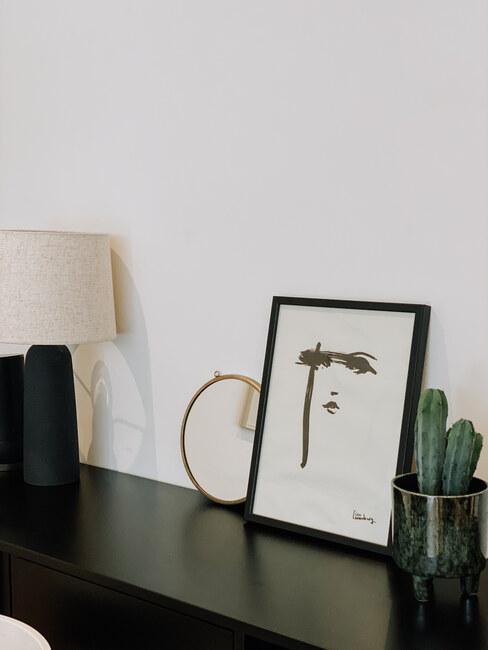 zwart dressoir met fotolijst en plant