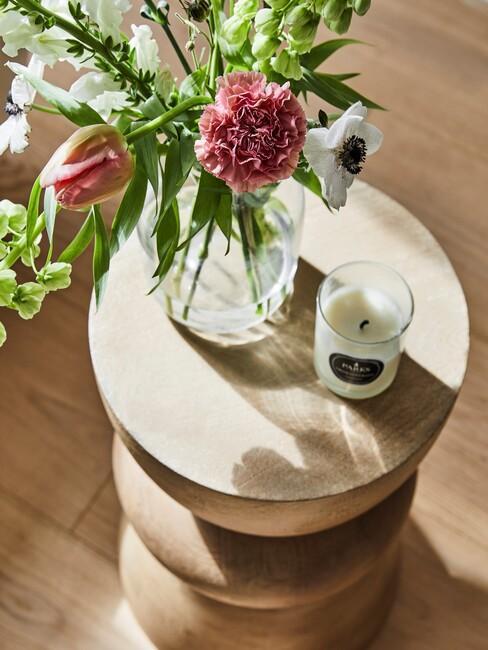 houten bijzettafel met bloemen en witte kaars