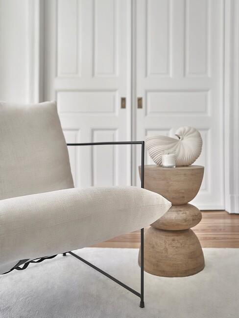 beige stoel met zwarte poten en houten bijzettafel