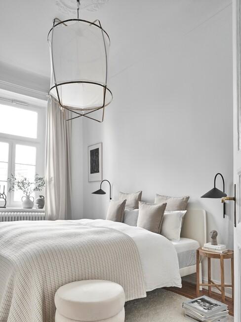 beige bed met witte plafondlamp