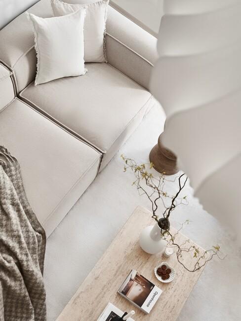 beige bank met houten tafel en witte vaas
