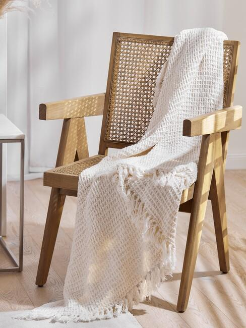 houten stoel met beige deken