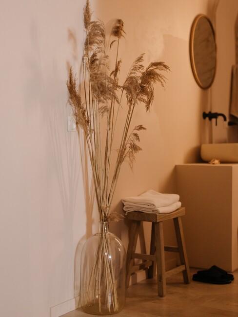 houten kruk met grote glazen vaas met droogbloemen