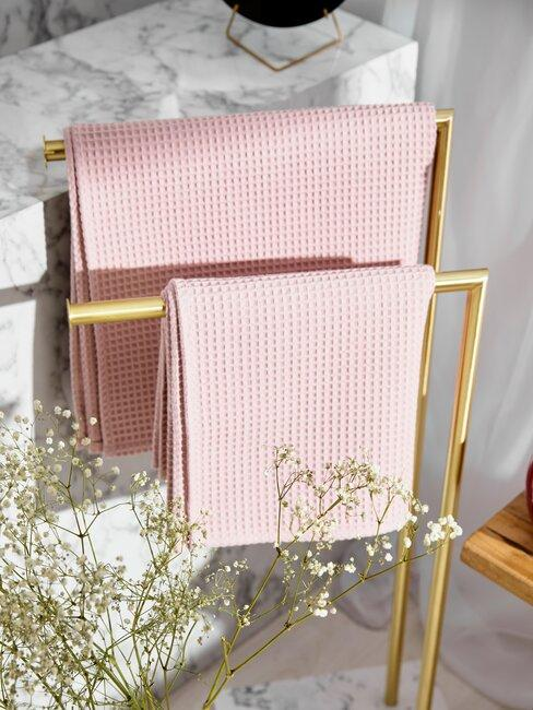 roze handdoeken aan gouden rek