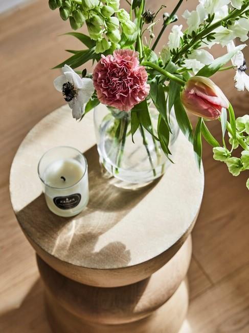 houten ronde tafel met een vaas met veldbloemen