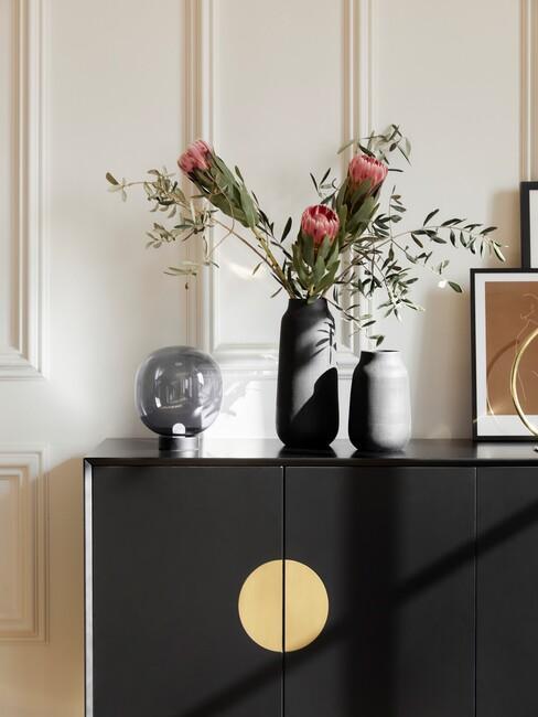 herfstbloemen in vaas op zwart dressoir