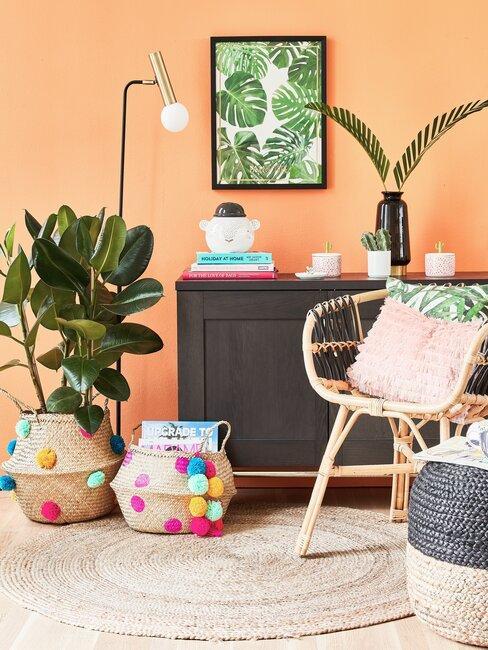 oranje muur met een zwarte kast met een rotan stoel