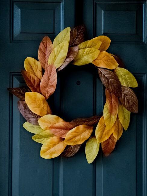 blauwe deur met gele herfstkrans