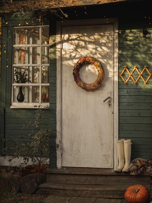 Herstkrans op een witte deur