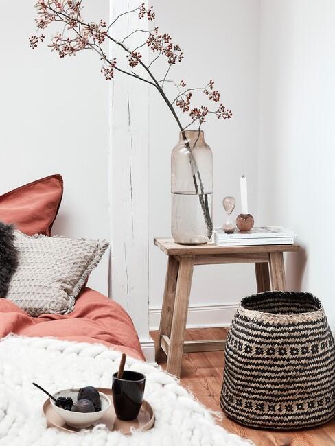 slaapkamer in herfstkleuren met rieten mand en houten kruk