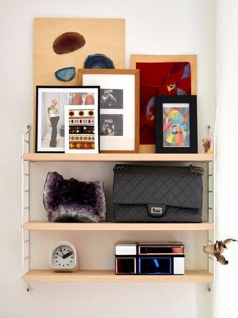 houten planken met fotolijsten en zwarte tas