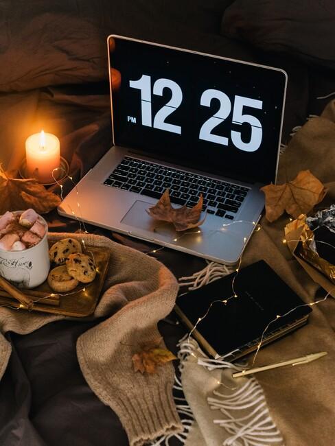 laptop op de grond met kaarsen