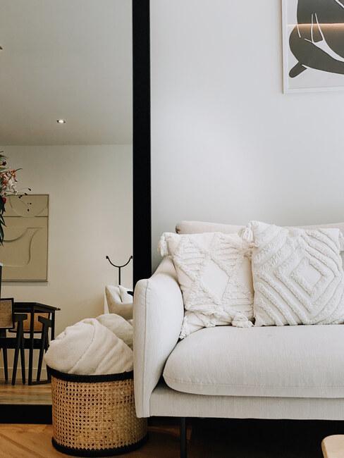 witte bank met beige kussens en zwarte spiegel