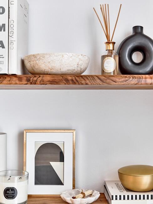 houten planken met zwarte vaas en gouden lijst