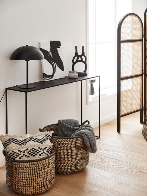 zwart wandmeubel met zwarte lamp en rieten manden