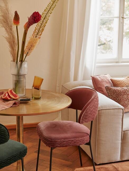 gouden ronde tafel met roze en groene eetkamerstoelen