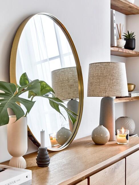 gouden ronde spiegel op een houten kast