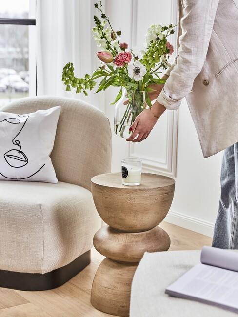 beige stoel met een houten kruk en een vaas bloemen