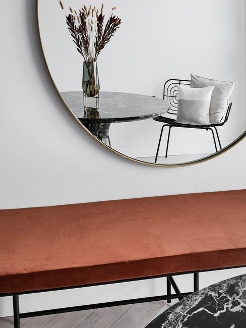 rood bankje met een ronde zwarte spiegel erboven