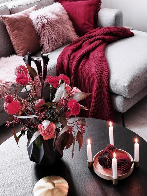 grijze bank met rode kussens en dekens met een ronde houten tafel