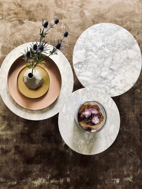 3 marmeren tafels met een gouden vaas met bloemen op een groen warm kleed