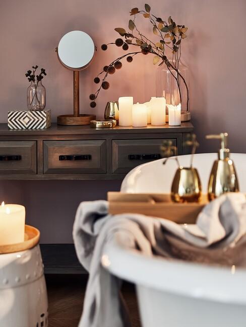 witte badkuip met een houten kast en een gouden spiegel