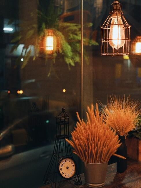 hangamp met een gouden vaas en droogbloemen