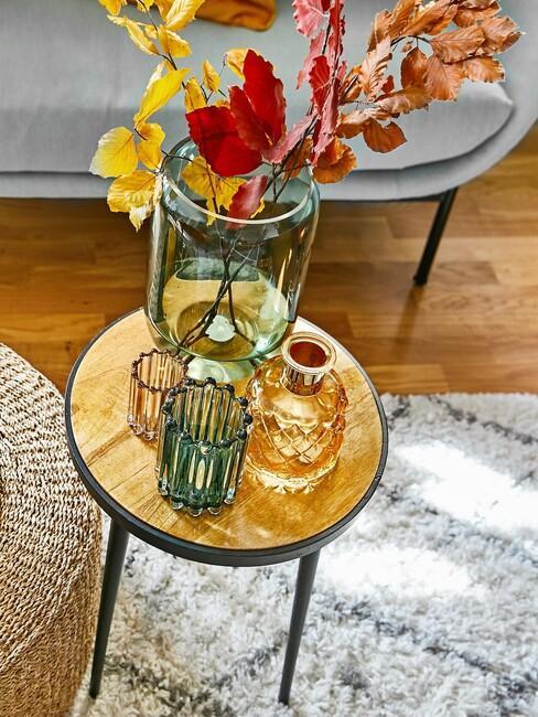 houten ronde tafel met een groene vaas