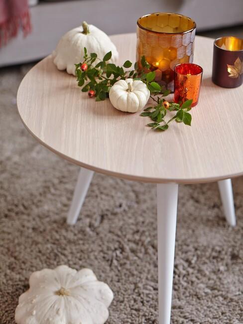 houten tafel met een oranje vaas en herfstbladeren