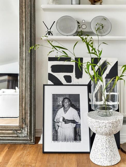 grote spiegel met zwarte fotolijst en witte bijzettafel