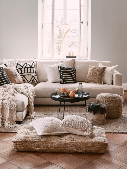 beige hoekbank met een ronde zwarte salontafel en rieten vloerkussens voor een slow living interieur
