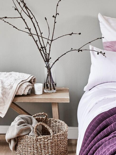 houten bank met mand van riet en lila dekbed