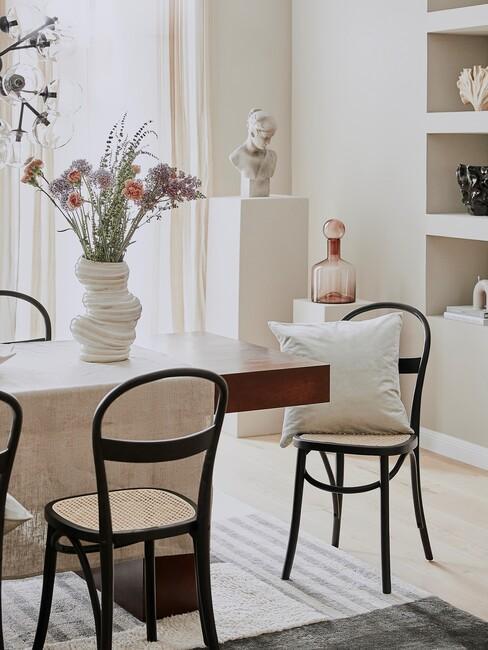 lange tafel met zwarte houten stoelen en paarse bloemen in een witte vaas