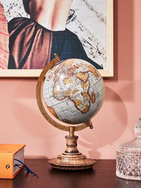 roze muur met een houten wereldbol met een houten fotolijst