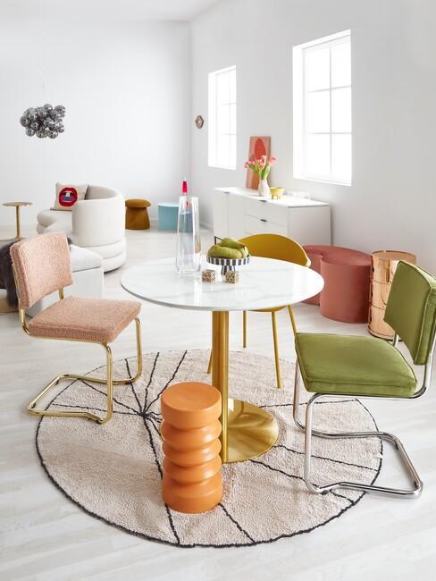 ronde marmeren tafel met groene en roze eetkamerstoelen