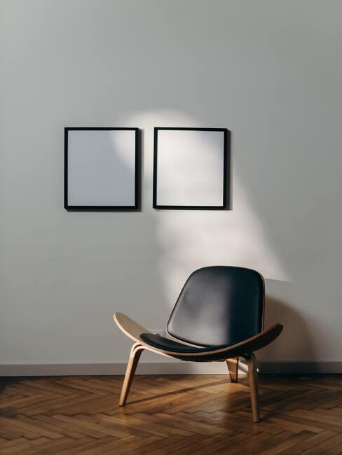 Houten stoel met zwarte kussens en zwarte fotolijsten