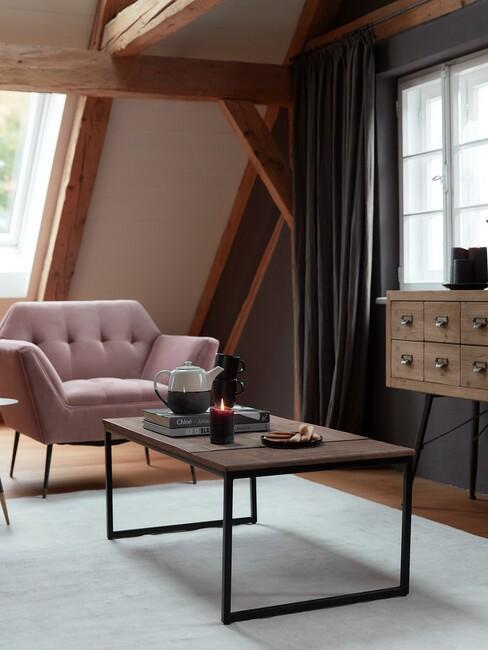 roze stoel met donker houten balken en zwarte tafel voor een industrieel-interieur