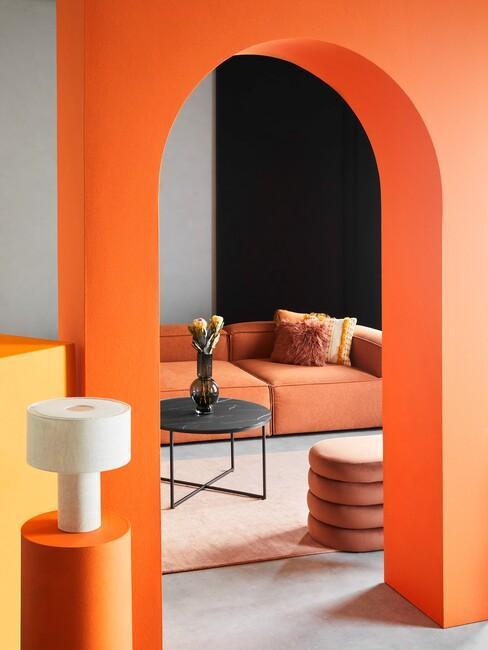 Oranje studio met een oranje hoekbank met een ronde zwarte salontafel