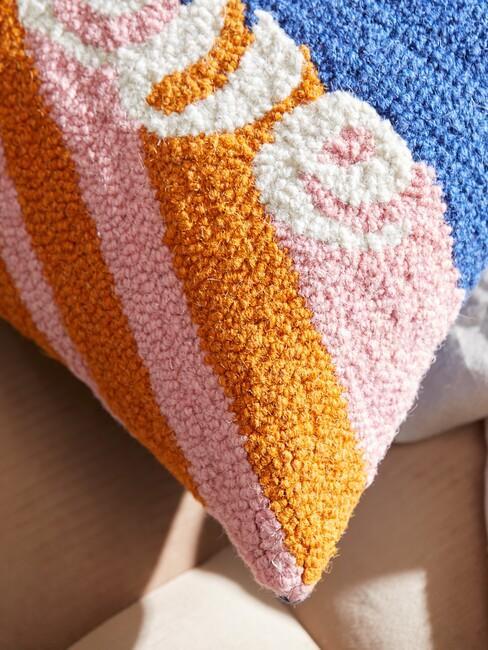 gekleurd kussen met blauw roze en oranje