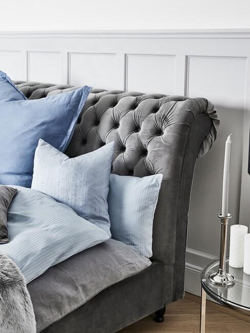 grijs bed met knopen erin en blauwe kussens