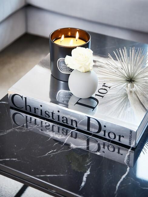 zilver dior boek op een zwarte marmere salontafel