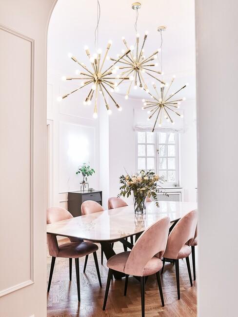 barok-stijl: witte tafel met roze stoelen en gouden hanglampen