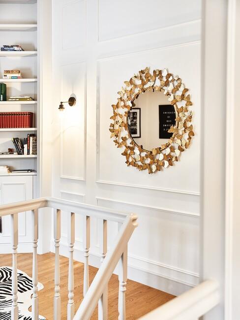 barok-stijl: gouden ronde spiegel in een witte gang
