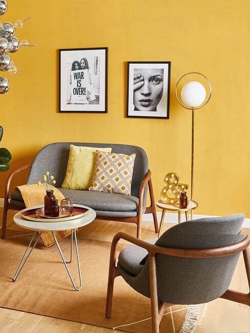 gele muur met een grijze bankset en houten poten