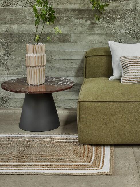 groene stoel met een rieten kleed en een zwart met bruine salontafel