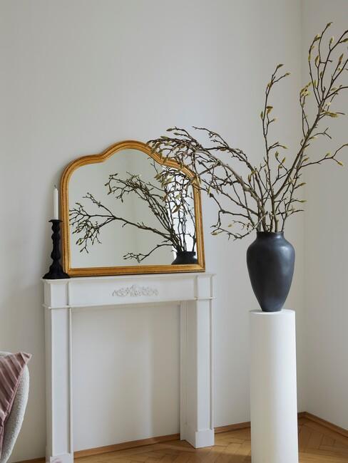 witte pilaar met een zwarte vaas en een gouden spiegel