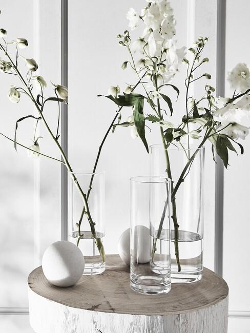 witte bloemen in glazen en witte vazen