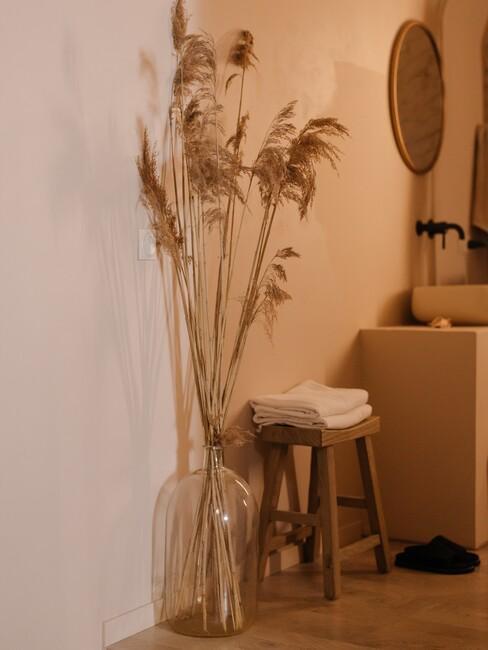 houten kruk met glazen vaas en droogbloemen