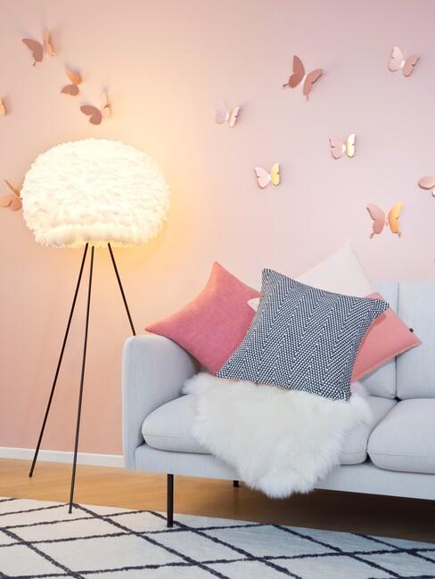grijze bank met een roze muur en gouden vlinders